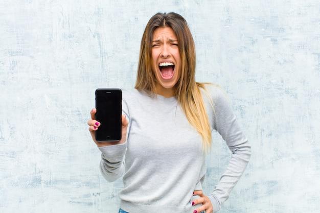 Молодая милая женщина с стеной grunge умного телефона