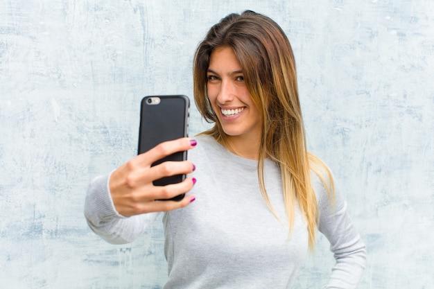 Молодая милая женщина с умным телефоном против стены grunge
