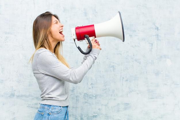 Молодая милая женщина с мегафоном против стены grunge