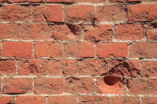 Старая красная кирпичная стена, предпосылка grunge.
