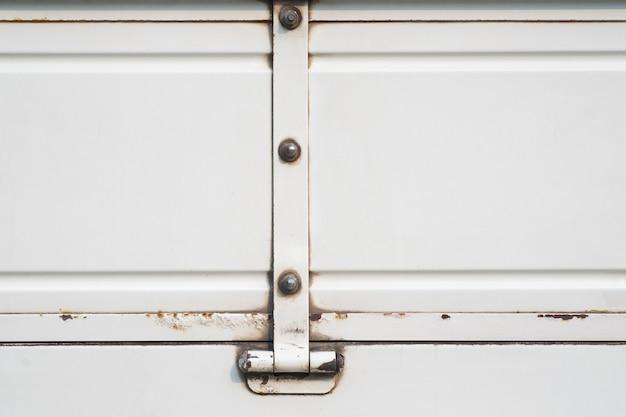 Старая белая тележка с предпосылкой ржавого, grunge металла белой краской и поверхностью.