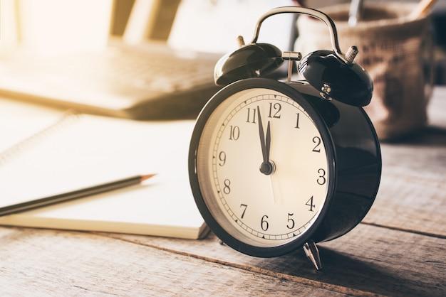 Ретро будильник на деревянной таблице с временем предпосылки grunge для концепции обеда.