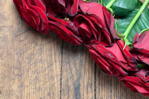 Граница красных роз на деревянной предпосылке grunge.