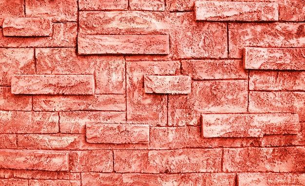 Тонизированная предпосылка grunge текстуры кирпичной стены цвета коралла.