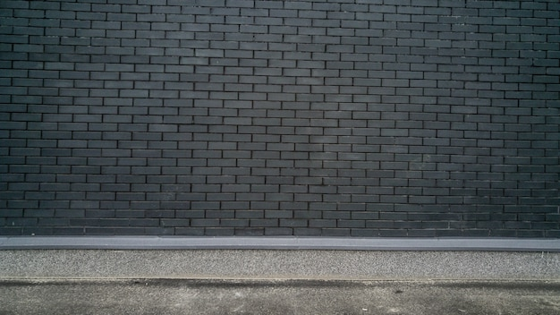 Grungy background with black brick wall and concrete ground. place for text
