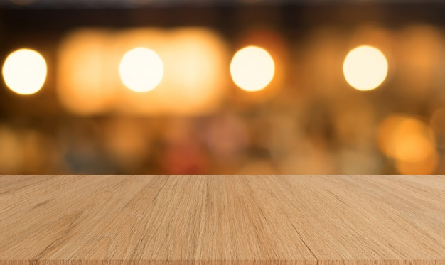 Grungy brown wood panel tabletop with blurred restaurant bar cafe light color background