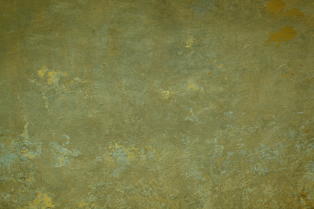 Grungy dark green painted wall  texture with fading paint and fine tracery of cracks in a full frame view.