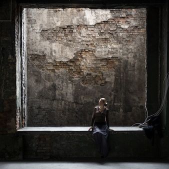 古い廃墟の建物の大きな窓に座っている孤独な女性の汚れたビュー