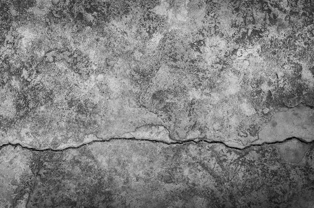 Шероховатая стена с большой трещиной на цементном полу, цементная большая трещина на темном фоне