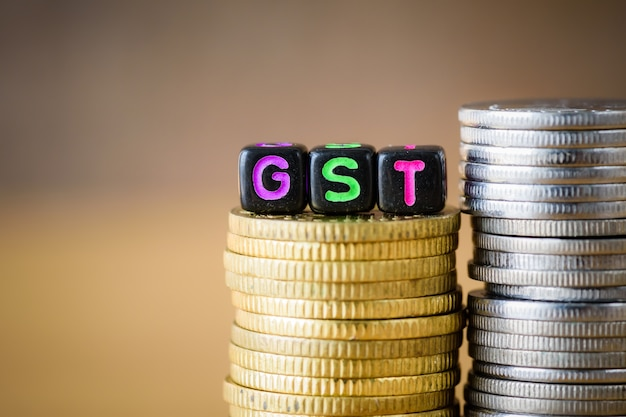 Gst concept with alphabet block on a gold stacked of coins.