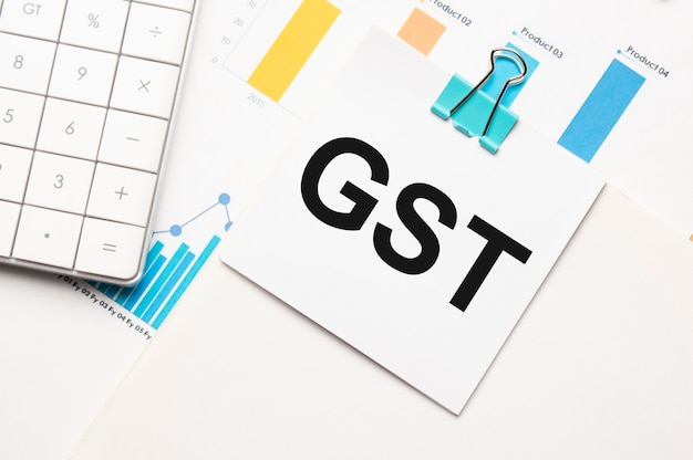 Gst text concept. office workplace table with calculator, graphs, reports and the text budget 2021 on a small piece of paper on multicolored background.