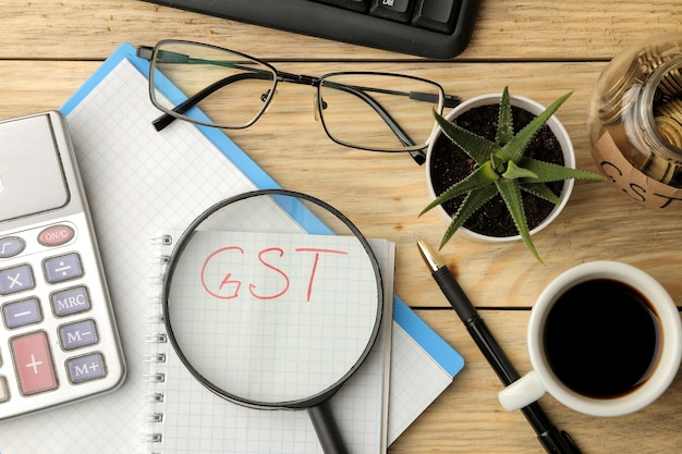Gst word in notebook under magnifying glass and calculator, pen and coffee on brown wooden background. view from above