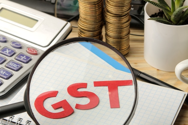 Gst word in notebook under magnifying glass and calculator, stack of coins on brown wooden background.