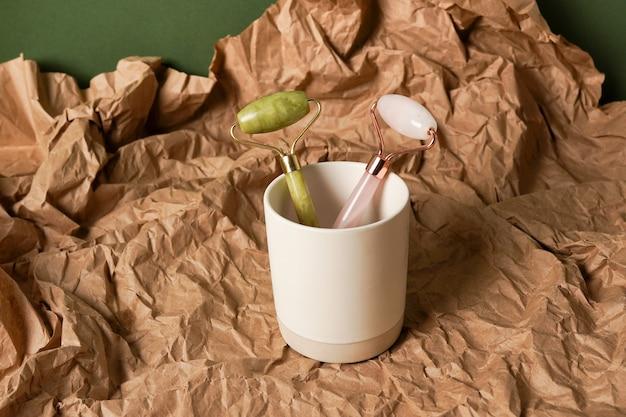 갈색 배경에 gua sha 옥 롤러입니다. 컵에 담긴 얼굴과 몸 관리를 위한 분홍색과 녹색 옥석