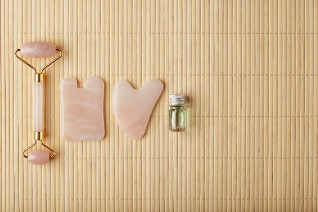 Гуа ша массаж, выполненный из натурального розового кварца-ролика, нефрита и масла, на бамбуковом фоне для ухода за лицом и телом.