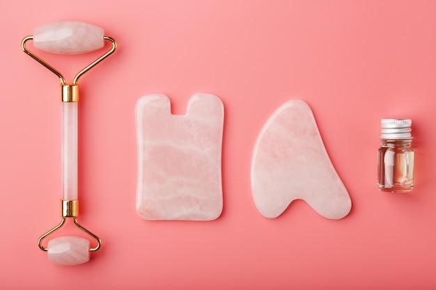 얼굴과 바디 케어를위한 분홍색 배경에 천연 핑크 쿼츠 롤러, 옥 돌과 기름으로 만든 구아 샤 마사지 도구. 중국 전통 의학의 일부 프리미엄 사진