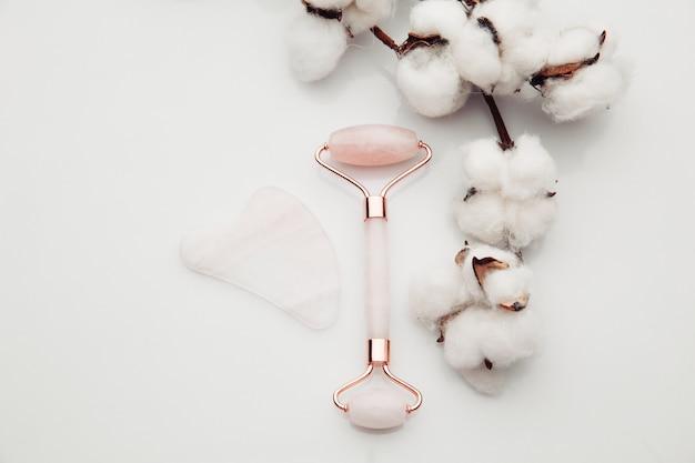 목화와 흰색 배경에 gua sha 마사지와 옥 롤러. 얼굴 및 바디 케어를위한 핑크 제이드 스톤