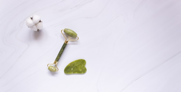 Gua sha roller and jade stone scraper on white background, free space for text
