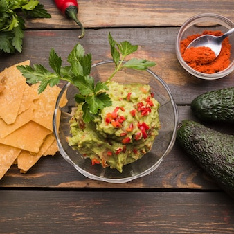 Guacamole among nachos and paprika with avocado