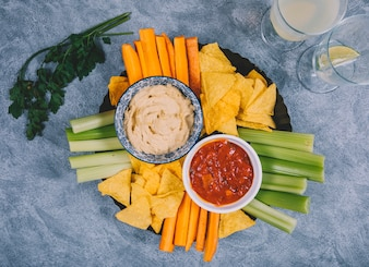 Guacamole and salsa sauce in bowl with carrot; celery stem; juice; coriander and tortilla chips over concrete background