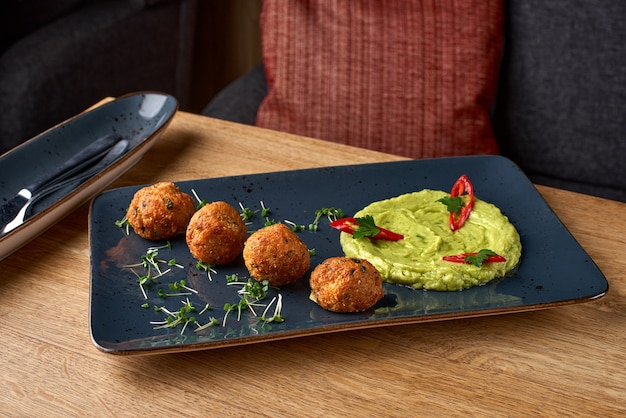 Guacamole and falafel dish on blue plate on a wooden table.