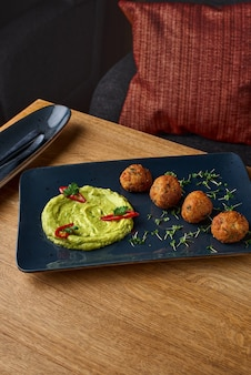 Guacamole and falafel dish on blue plate on a wooden table