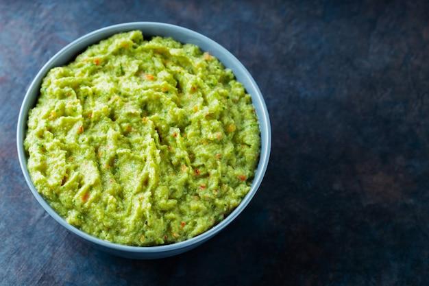 Гуакамоле в серой миске на темном фоне. чаша авокадо соуса гуакамоле со свежими ингредиентами. скопируйте пространство. вид сверху