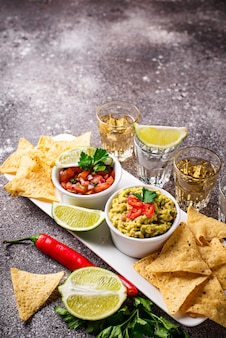 Guacamole, salsa, chips nachos and tequila