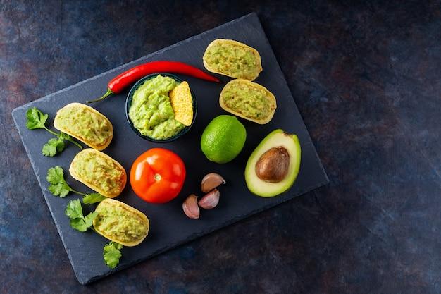 Соус гуакамоле, чипсы начос и ингредиенты на темном фоне. мексиканский соус гуакамоле с авокадо, ингредиентами и кукурузными начос. скопируйте пространство. вид сверху
