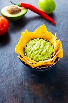Соус гуакамоле с ингредиентами авокадо, перцем, лаймом и кукурузными начос на темном фоне. гуакамоле с ингредиентами и чипсами начос из тортильи. копировать пространство