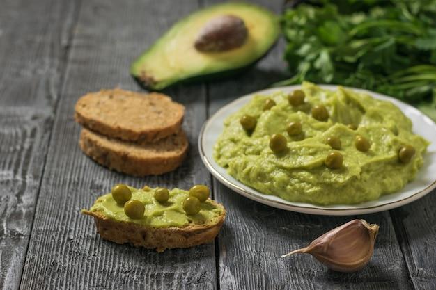 소박한 테이블에 녹색 완두콩과 빵을 곁들인 과카몰리. 다이어트 채식 멕시코 음식 아보카도. 날 음식.