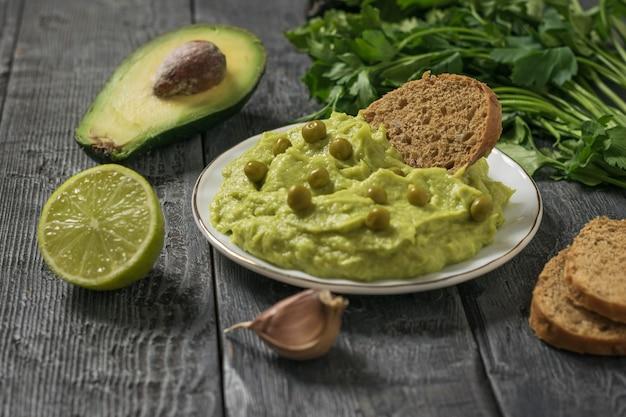 나무 테이블에 있는 흰색 접시에 녹색 완두콩, 파슬리, 라임이 있는 과카몰리. 다이어트 채식 멕시코 음식 아보카도. 날 음식.