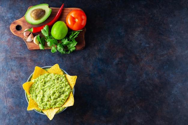 Гуакамоле с ингредиентами и чипсами начос из тортильи. авокадо гуакамоле с ингредиентами перец, лайм и кукурузные начо на темном фоне. скопируйте пространство. вид сверху