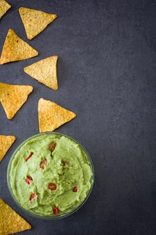 Guacamole with nachos on black surface top view