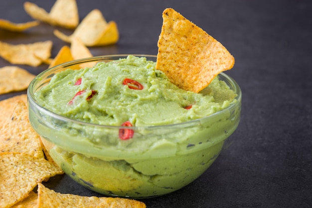 Guacamole with nachos on black surface