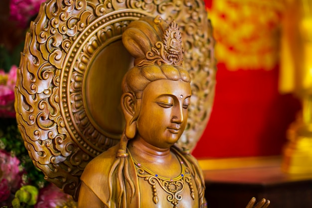 Guanyin close up face carved from beautiful wood chinese temple in thailand