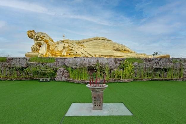 푸른 하늘과 잔디 배경에 거짓말 부처님의 관음 황금 동상