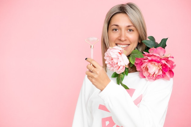 Guasha roller in hand of blonde woman disfocused on pink background in studio with flowers, copy space, stock photo