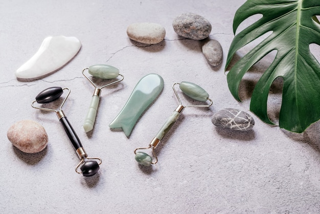 얼굴 마사지에 사용되는 guasha 스파 도구, 자갈 돌 및 열대 몬스 테라 잎이있는 옥 guasha 마사지 롤러 및 스크레이퍼