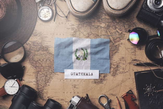 Guatemala flag between traveler's accessories on old vintage map. overhead shot