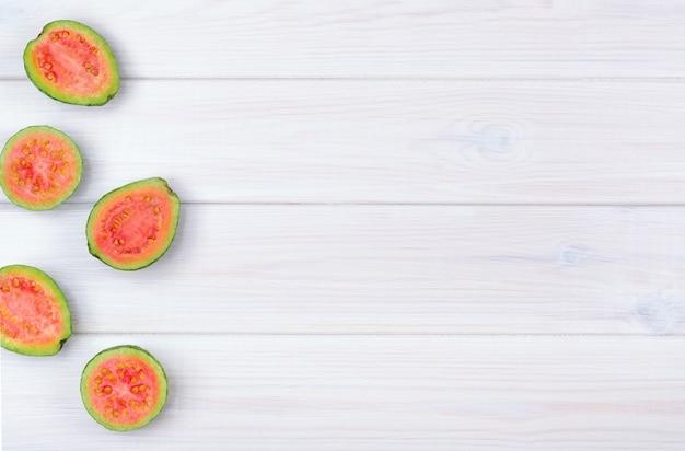 Плоды гуавы, изолированные на белом фоне деревянные