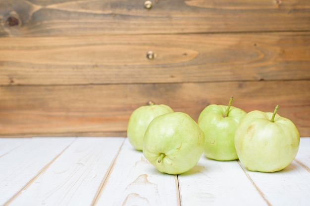 Guavas on white wooden table.