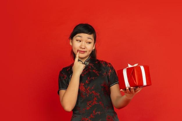 선물이 뭔지 맞춰보세요. 해피 중국 설날. 빨간색 배경에 고립 된 아시아 젊은 여자의 초상화. 전통 옷을 입은 여성 모델이 행복해 보입니다. 축하, 휴일, 감정. copyspace.