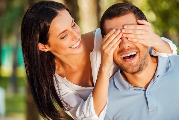 누군지 맞춰봐? 아름다운 젊은 여성이 남자 친구의 눈을 가리고 야외에 서 있는 동안 웃고 있습니다.