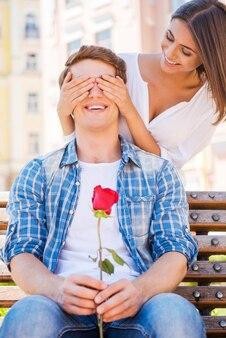누군지 맞춰봐? 남자가 벤치에 앉아 빨간 장미를 들고 있는 동안 남자친구의 눈을 가리고 웃고 있는 아름다운 젊은 여자