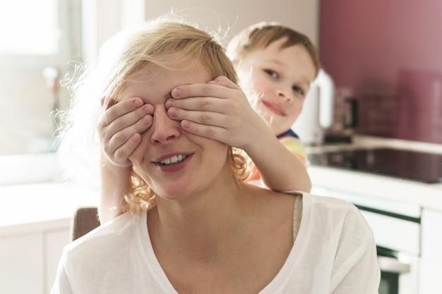Угадай кто? симпатичный мальчик закрывает глаза своей матери на кухне.