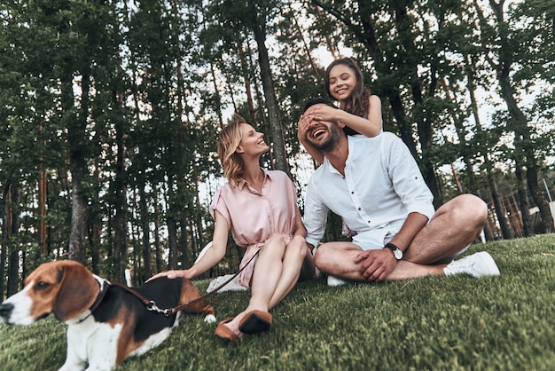누군지 맞춰봐! 공원의 잔디에 앉아 웃고 있는 3명의 행복한 젊은 가족