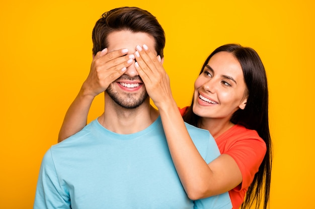 誰だと思いますか? 2人の愛らしい男女性の人々の写真目を閉じてロマンスサプライズ訪問着用カジュアルブルーオレンジtシャツ孤立した黄色の色の壁