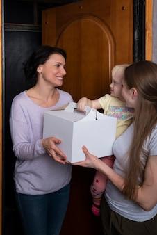 ゲストはケーキの箱を持ってきました。若い母と子は贈り物でゲストを歓迎します。