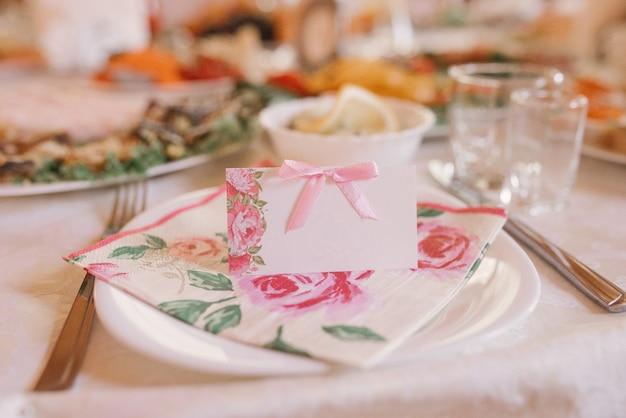 연회 웨딩 테이블에 분홍색 꽃으로 게스트 카드. 웨딩 장식
